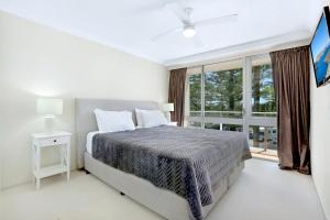 A bed or beds in a room at Pacific Regis Beachfront Holiday Apartments