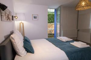 A bed or beds in a room at L escapade- Home-One