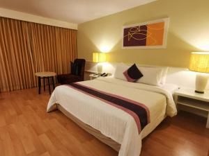 A bed or beds in a room at Tongtara Riverview Hotel