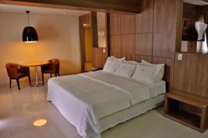 A bed or beds in a room at Agulhon Hotel