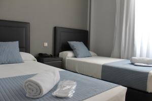 Ein Bett oder Betten in einem Zimmer der Unterkunft Hotel Barajas Plaza