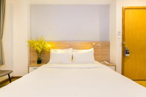 A bed or beds in a room at Joviale Hotel