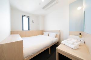 A bed or beds in a room at WeBase Hiroshima