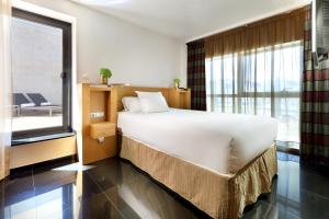 A bed or beds in a room at Hesperia Barcelona Fira Suites