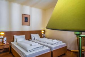 A bed or beds in a room at Zichy Park Hotel
