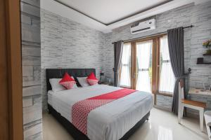 A bed or beds in a room at OYO 1769 Mahayun Guest House Syariah