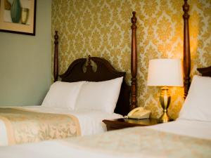 A bed or beds in a room at The Abbeyleix Manor Hotel