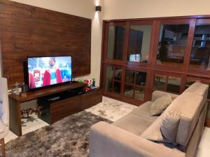 Uma TV ou centro de entretenimento em Casa Retrô Chique Bananeiras - Cond Yes Banana