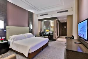A bed or beds in a room at Hili Rayhaan by Rotana