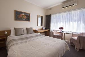 A bed or beds in a room at Cooma Motor Inn