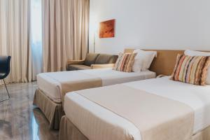 A bed or beds in a room at Agalia Hotel