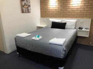 A bed or beds in a room at Chermside Motor Inn