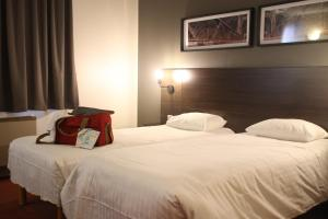 A bed or beds in a room at Orly Superior Hotel