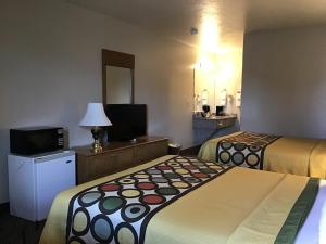 A bed or beds in a room at Super 8 by Wyndham Hurricane Zion National Park
