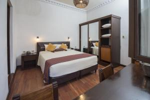 A bed or beds in a room at La Casona Hotel Boutique