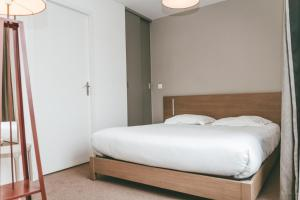 A bed or beds in a room at Terres de France - Appart'Hotel Quimper Bretagne