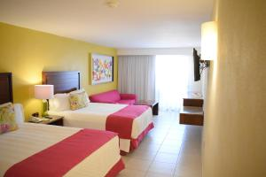 A bed or beds in a room at Canto del Sol Puerto Vallarta All Inclusive