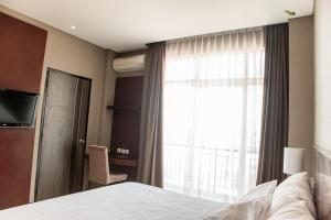 A bed or beds in a room at Karlita Hotel Tegal