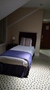 A bed or beds in a room at Basingstoke Country Hotel & Spa