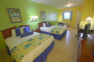 A bed or beds in a room at Plantation Suites and Conference Center