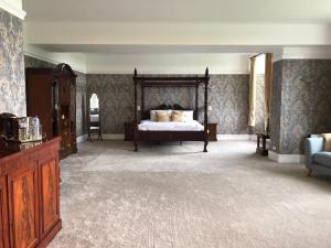 A bed or beds in a room at Oswald House Hotel