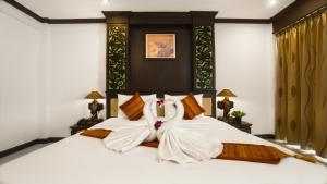 A bed or beds in a room at Aonang Orchid Resort