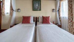 A bed or beds in a room at Sarova Lion Hill Game Lodge