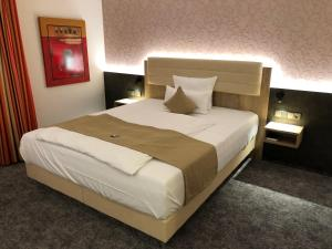 A bed or beds in a room at Hotel Merkur