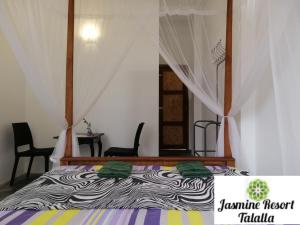 A bed or beds in a room at Jasmine Resort Thalalla