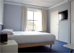 A bed or beds in a room at Belgische Loodsensociëteit