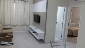 A television and/or entertainment centre at Le Village Flats Hotel e Business