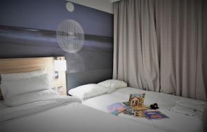 A bed or beds in a room at Novotel London Stansted Airport
