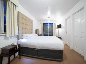 A bed or beds in a room at OYO George Hotel