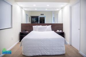 A bed or beds in a room at Crystal Beach Suites Oceanfront Hotel