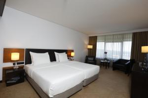 A bed or beds in a room at Montebelo Viseu Congress Hotel