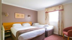 A bed or beds in a room at Holt Lodge Hotel