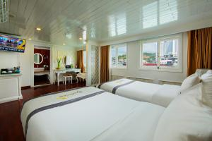 A bed or beds in a room at Signature Royal Halong Cruise