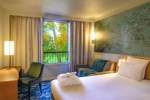 A bed or beds in a room at Novotel Domaine de Maffliers