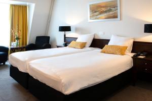 Een bed of bedden in een kamer bij Golden Tulip L'Escaut Terneuzen