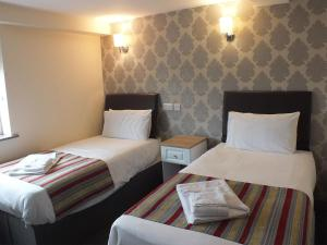 A bed or beds in a room at The Fazeley Inn