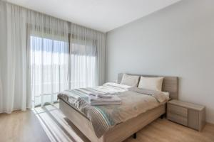 A bed or beds in a room at Sweet Home - Prestigia Golf City