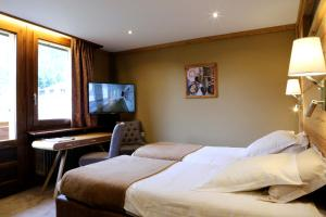 A bed or beds in a room at Les Gourmets - Chalet Hotel