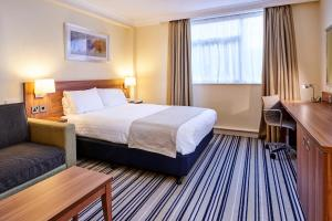 A bed or beds in a room at Holiday Inn Leeds Garforth