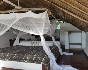 A bed or beds in a room at Kae Michamvi Sunset Bungalows