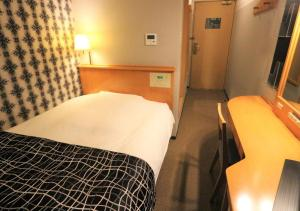 A bed or beds in a room at APA Hotel Kanazawa Chuo