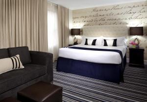 A bed or beds in a room at Kimpton George Hotel