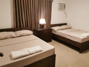 A bed or beds in a room at The Resthouse Laiya