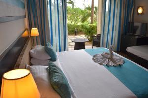 Een bed of bedden in een kamer bij Pearle Beach Resort & Spa