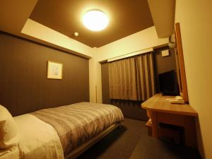 A bed or beds in a room at Hotel Route-Inn Yokote Inter