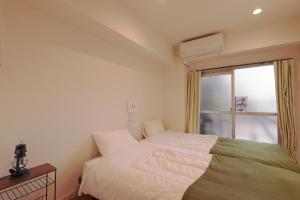 A bed or beds in a room at V.Close to Shinjuku Kabukicho/Korean Town/FrWIFI D